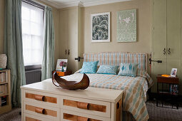 Chest of drawers at foot of bed with headboard and matching bedspread