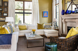 Scatter cushions on pale sofa set, rustic coffee table and armchair in front of fireplace