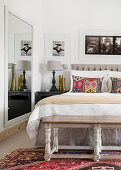 Tapestry-style scatter cushions on double bed and large mirror in bedroom