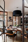 View through open glass door into dining room with round set table