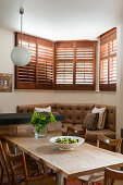 Chairs around wooden table in front of corner bench in bay window with shutters
