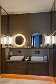 Two round mirrors above twin washstand in bathroom