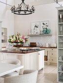 Bowl of flowers on island counter in bright country-house kitchen