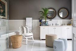 Pale furnishings and dark walls in elegant bathroom