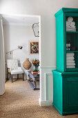 Towels in turquoise dresser next to open doorway