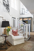 White, loose-covered armchair and side table next to foot of staircase