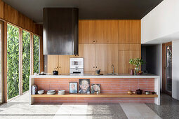 Kitchen island in front of an oak kitchen in an open living room