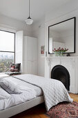 Double bed with quilt in front of fireplace in white bedroom