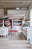 White kitchen, built-in shelves and artwork in an open living room with concrete ceiling