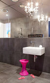 Sinks, pink stools and chandeliers in the bathroom with dark tiles