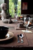 Rustikal gedeckter Tisch in Brauntönen mit Buddha