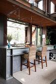 Offene Küche im Industriestil mit Kücheninsel aus Stahlträgern