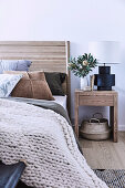 Wooden bed and matching bedside table in bedroom