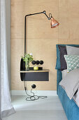 Lamps on bedside table against wall clad in plywood panels