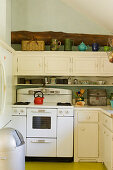 Old cooker in small, country-house-style kitchen