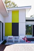 Sonnige Terrasse vor einem Haus mit bunter Fassadenverkleidung