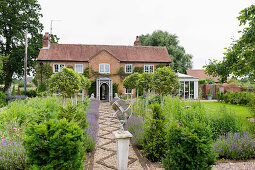 Gravel path flanked by flowerbeds leading to renovated English country house