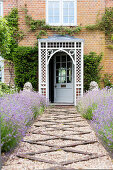 Gravel path lined by lavender beds leading to front door of country house with porch
