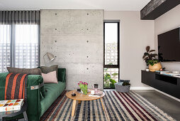 Green velvet sofa in front of concrete wall in modern living room
