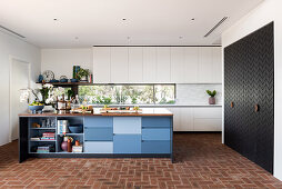 Large kitchen with various kitchen fronts and brick floor