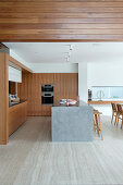 Open kitchen with wooden cladding and kitchen island in architect's house