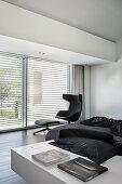 Desingersessel mit Fußschemel vor Terrassentür in schwarz-weißem Schlafraum
