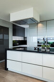 Modern, black-and-white kitchen with glossy cabinets