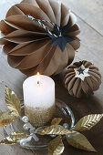 Original arrangement of handcrafted honeycomb balls and golden leaves around candle