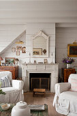 Slip covered armchairs with Gustavian style fireplace in tongue and groove living room of 18th century conversion