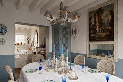 Silverware candlesticks on dining table with corner cabinet and 18th century French trumeau mirror