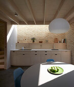 Round table in open-plan modern kitchen with counter, brick wall and skylight