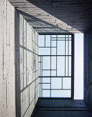 View up through skylight in board-formed concrete stairwell