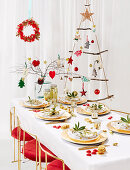 Set Christmas dining table in front of suspended DIY Christmas tree made from rope and branches