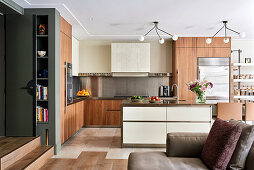 White island counter in open-plan wood and stainless steel kitchen