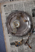 Old newspaper, vintage pewter plate, wristwatch, jewellery and spectacles