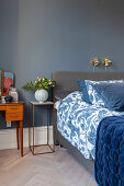 Dressing table and vase of flowers on slimline table next to grey box spring bed with blue-and-white bed linen