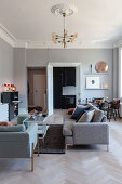 Pale grey walls and stucco friezes in living room of renovated period apartment