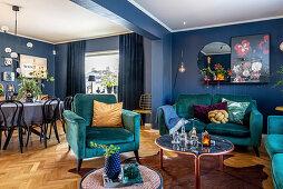 Petrolfarbene Polstergarnitur in offenem Wohnraum mit blauen Wänden