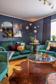 Petrolfarbene Polstergarnitur im Wohnraum mit blauen Wänden