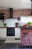 Island with dusky-pink wooden front and vintage-style wallpaper above kitchen counter