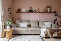 Chaise couch in living room with pastel-pink walls