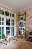Antique gilt-framed mirror against brick wall