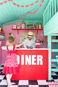 Children at counter in play house made to look like fifties diner