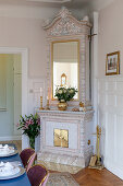 Antique tiled stove in grand interior with panelled walls