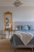 Gilt-framed mirror and console table next to bed