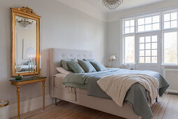 Gilt-framed mirror next to bed in elegant bedroom in period building