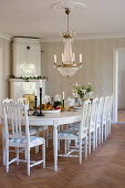 Corner tiled stove and large white dining table with wooden chairs in dining room of manor house