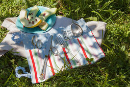 Hand-sewn cutlery roll and plate of honeydew melon