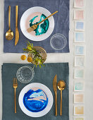 Watercolour-effect plates and gilt cutlery on set table
