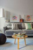 Round coffee table in front of grey sofa with graphic patterns on scatter cushions